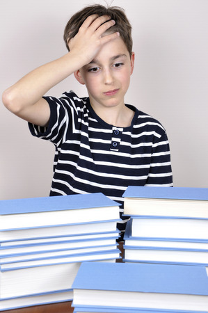 Surprised and astonished young boy holding his forehead with one hand and sitting at the table with books wondering how much he has to read photo