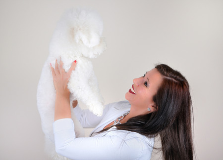 bichon: Smiling glamorous woman in white holding white fluffy dog isolated on gray background Stock Photo