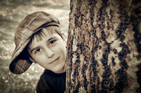 Young boy with newsboy cap sneaking behind a tree and playing detective. Vintage style photo Stok Fotoğraf