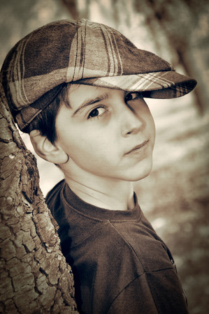 newsboy cap: Young boy with newsboy cap leaning on a tree and playing detective. Vintage style photo