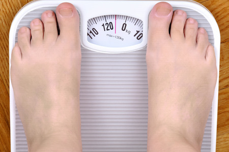 woman on scale: Barefoot overweight person standing on the scale