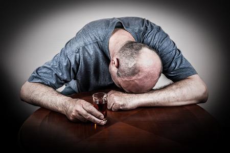 borracho: Hombre borracho durmiendo en la mesa con la cabeza en la mano y con un vaso de bebida de alcohol Foto de archivo