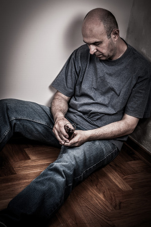 hombre solitario: Hombre borracho sentado en el suelo para dormir y con un vaso de bebida de alcohol