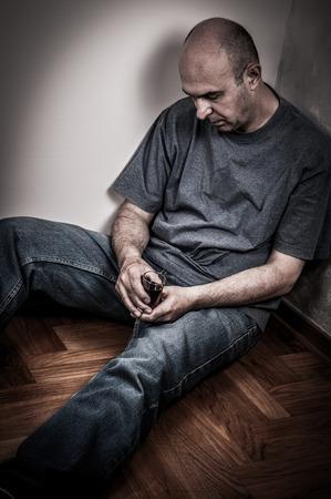 visage homme: Homme ivre assis sur le sommeil de-chaussée et tenant un verre de boisson de l'alcool