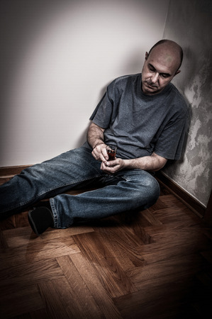 intoxication: Drunk man sitting on the floor sleeping and holding a glass of alcohol drink