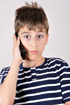 smart boy: Surprised and wondering young boy talking on his smart phone