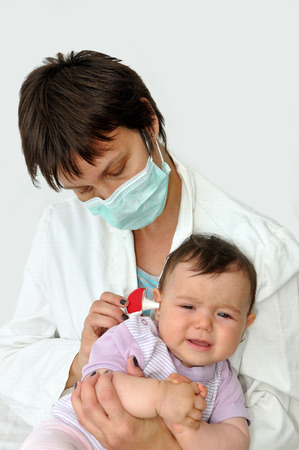 protective mask: Doctor pediatrician with protective mask examining baby girl