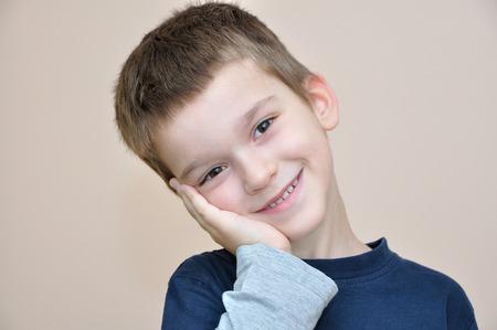 cheek to cheek: Cute young smiling boy holding hand on cheek
