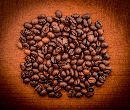 are taken: Heap of coffee beans on the brown table. Image taken from above.