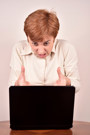 gesticulating: Angry businesswoman making a grimace, gesticulating with her hands and looking at a laptop Stock Photo