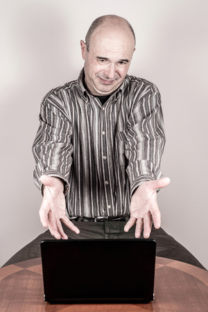 grimace: Angry and nervous businessman making a grimace and showing a laptop with his hands