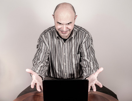gesticulating: Angry and nervous businessman making a grimace, gesticulating with his hands and looking at a laptop