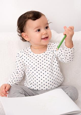 jardin de infantes: ni�a sentada en la cama y dibujar con un l�piz de color sobre el papel de la sonrisa Foto de archivo