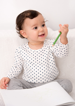 Smiling baby girl sitting on the bed and drawing with a colored pencil on the paper