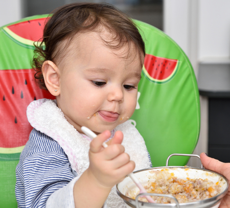 eat smeared baby: Smeared hungry baby girl eating baby food with plastic spoon Stock Photo