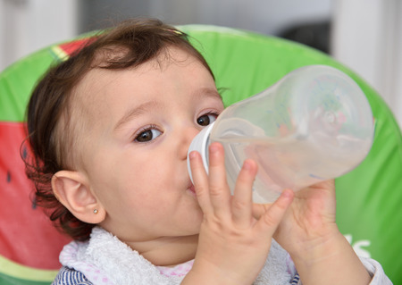 nipple young: Thirsty baby girl drinking water from the feeding bottle