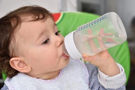 sediento: Bebé sediento que bebe de la botella de alimentación