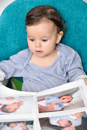 family memories: Cute smiling baby girl looking at the photo album with the picture of herself
