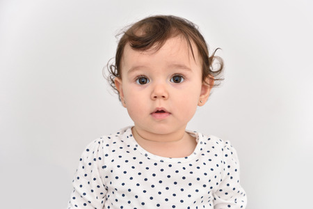 baby isolated: Portrait of a cute baby girl with beautiful big brown eyes. Isolated on a light gray background.