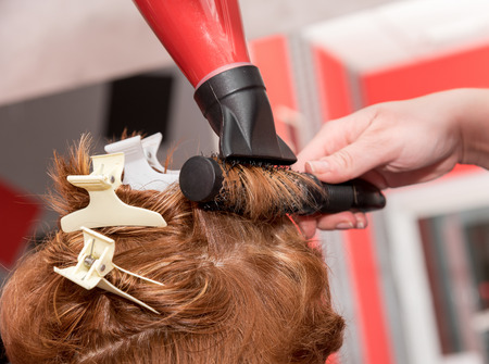 A hairdresser curling a lock with brush and drying a hairdryer. Selective focus. Stock Photo
