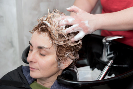 health service: A hairdresser washing hair of a woman with shampoo. Selective focus.