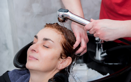 shampooing: A hairdresser rinsing hair of a woman after shampooing. Selective focus.