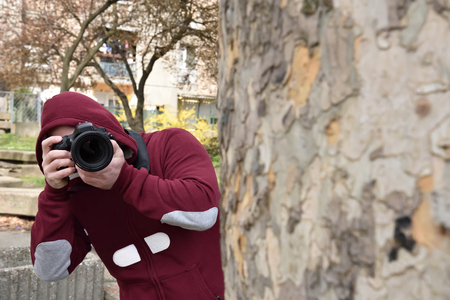 lurking: Mysterious paparazzi photographer with the hood on his head lurking behind the tree