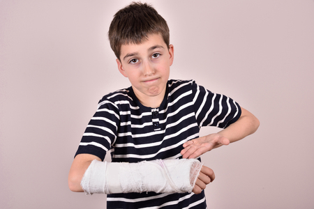 ゆがんだ顔を作ると石膏で壊れた腕を示す少年