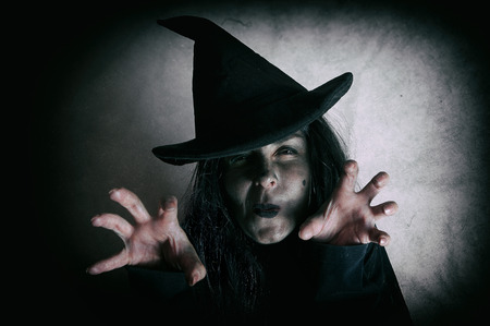 Halloween witch. Low key. Computer added dirt, scratches, grain and vignette. Stock Photo