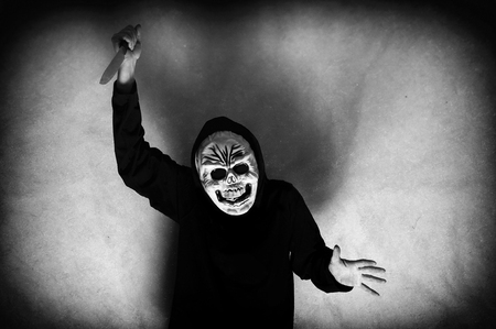 death head holding: Woman in black with a human skull mask holding a knife. Low key. Computer added dirt, scratches, grain and vignette. Stock Photo