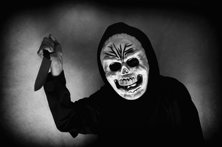 skull mask: Woman in black with a human skull mask holding a knife. Low key. Computer added dirt, scratches, grain and vignette. Stock Photo