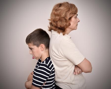 怒っている母と息子が互いに背を向けて彼の舌を突き出して