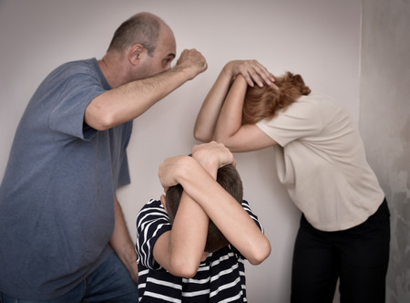 bending down: Domestic violence.  Young boy bending down and covering his head with his hands while the father is threatening his mother. Focus on the young boy.