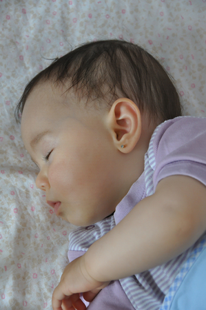 ambient light: Tired baby girl sleeping. Selective focus. Ambient light. Stock Photo