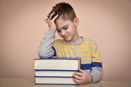 displeased: Sad and displeased young boy sitting at the table with books and holding his forehead with one hand