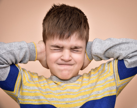 hands covering ears: Young boy with closed eyes covering ears with hands Stock Photo