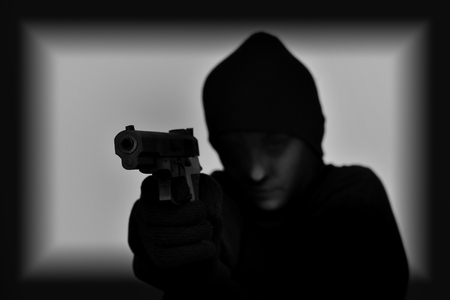 holding gun to head: Female robber with black tights over her head holding a gun and aiming. Black and white. Low key. Selective focus.