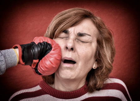 wallop: Woman being punched with red boxing glove in her face. Computer added  dust, scratches, grain and vignette.