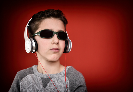 pubertad: Young boy with headphones and sunglasses listening to music and enjoying. Isolated on the red background Foto de archivo