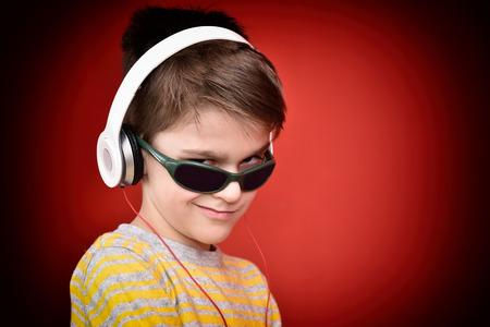 Young boy with headphones listening to music, enjoying and looking from under sunglasses. Isolated on the red background.