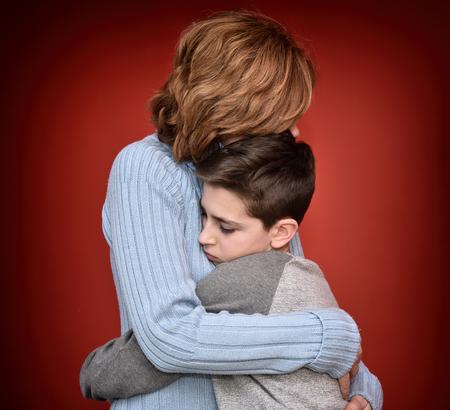 素敵な母親を抱いて目を閉じて悲しい少年 写真素材