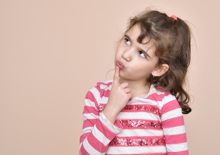 Thoughtful cute young girl with index finger on her mouth Stock Photo