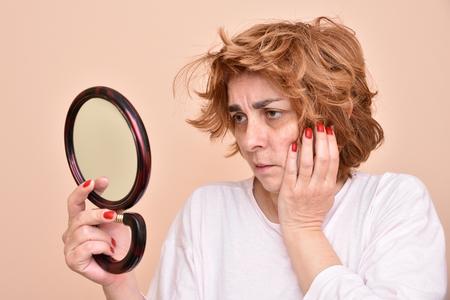 不幸と不満中年の女性彼女の肌とミラーでボサボサの髪を見て