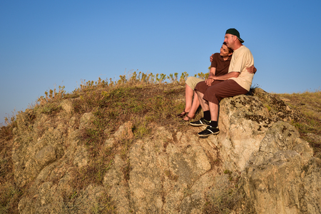 Couple in love sitting, hugging and enjoying on the top of the mountain in the sunset Stock Photo