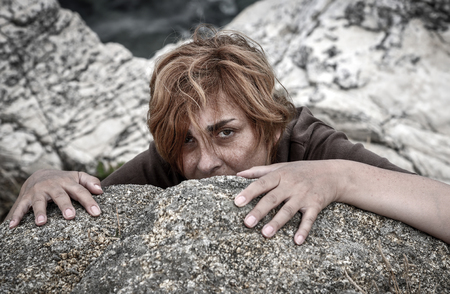 Frightened woman hiding behind the rock. Selective focus. Stock Photo