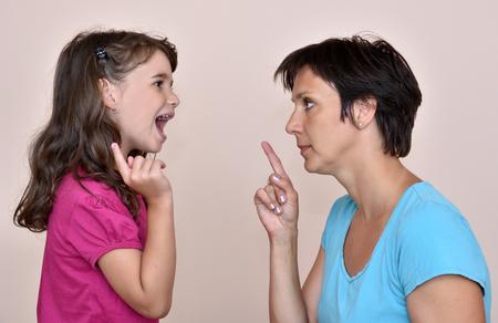 Mother and daughter arguing with index fingers up Reklamní fotografie