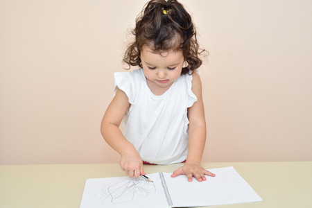 drawing room: Cute young girl drawing with a pencil in the notebook Stock Photo