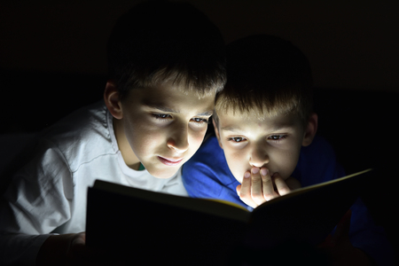 Two brothers reading a book hiding in the dark and using a torch light. Selective focus.