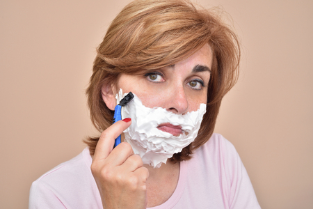 Sad middle aged woman shaving her face with a razor 版權商用圖片