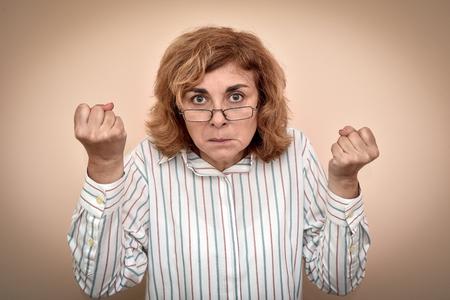 Mujer de mediana edad enojada y furiosa con anteojos amenazando con sus puños Foto de archivo
